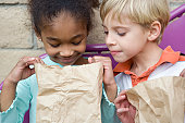 Boy looking in friends lunch bag at recess