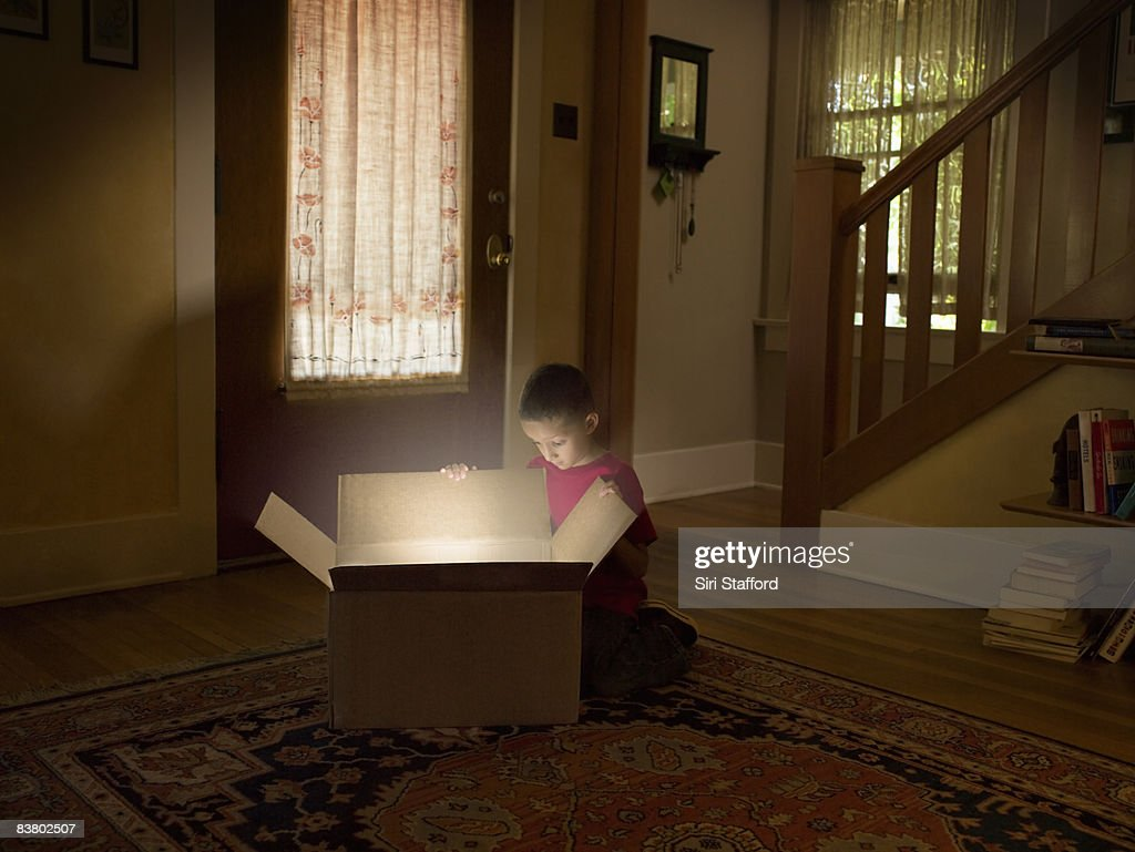 Boy looking into box with light illuminating out : Stock Photo