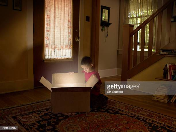Boy looking into box with light illuminating out