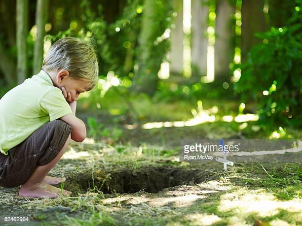 Junge auf der Suche in Grab von Haustier.