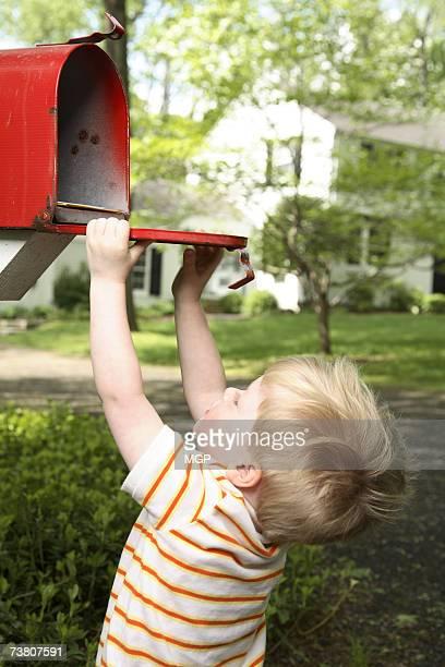 Boy (2-3) looking into mailbox