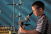 Boy Looking Into Microscope In Chemistry Class
