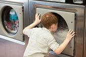 Boy looking into washing machine