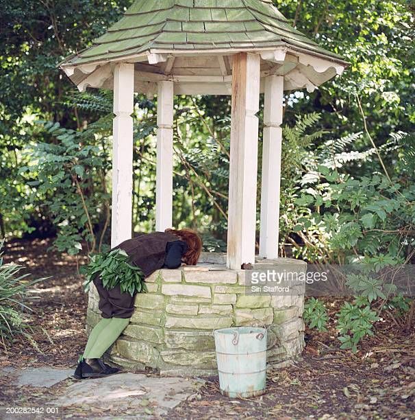 Boy (6-8) looking into wishing well