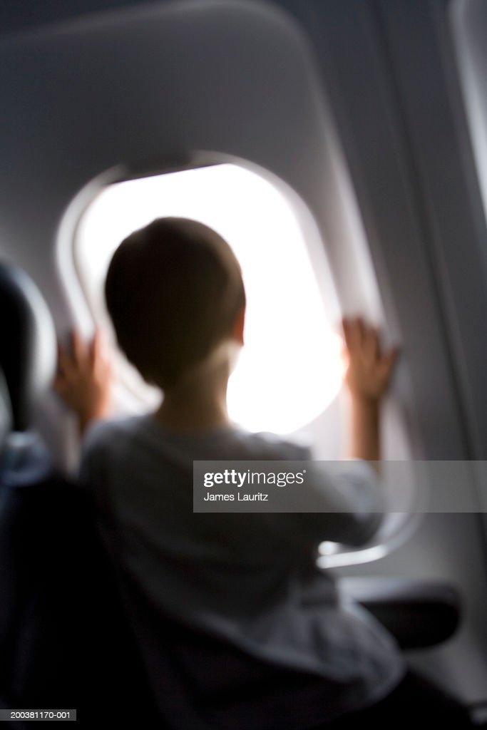 Boy (3-5) looking out aeroplane window, rear view (defocussed)