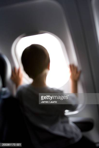 Boy (3-5) looking out aeroplane window, rear view (defocussed)