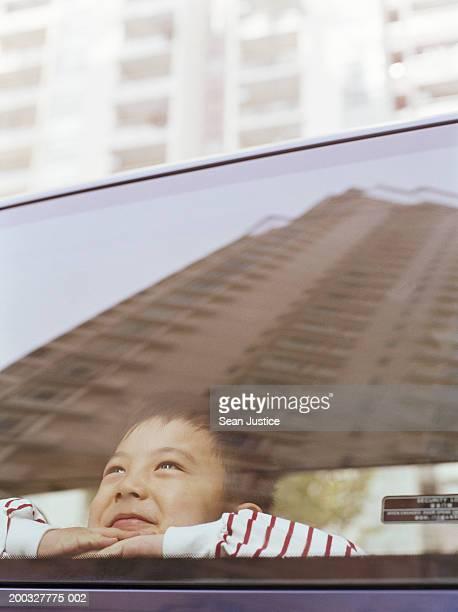 Boy (4-6) looking out car window