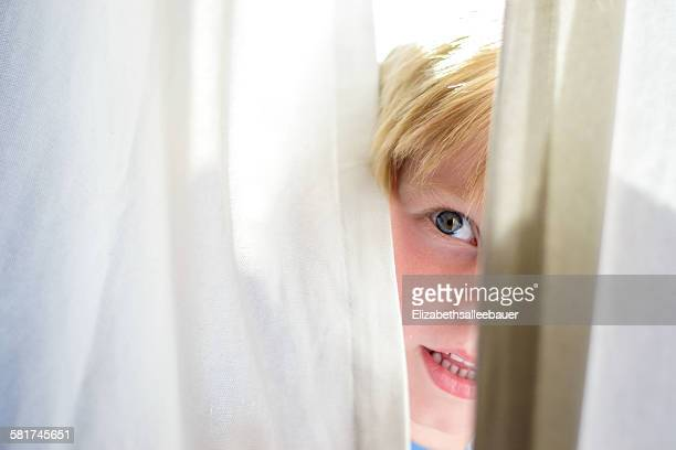 Boy looking out from behind a curtain