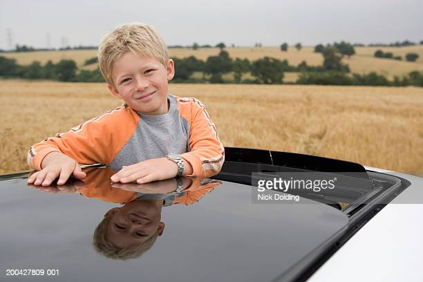 Boy (8-9 years) looking out of car sunroof, smiling, portrait