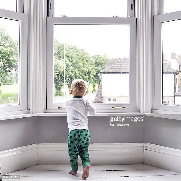 Young boy at home looking out of window