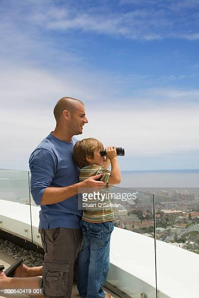 Boy (4) looking out over city with binoculars, father holding him