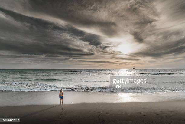 Boy looking out to sea and dramatic sky from Venice Beach, California, USA