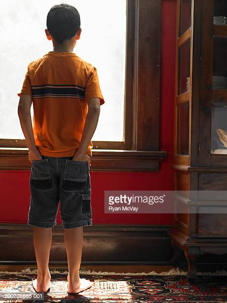 Boy (8-10) looking out window, hands in pockets, rear view