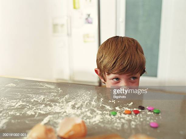 Boy (4-6) looking over edge of kitchen counter covered in flour