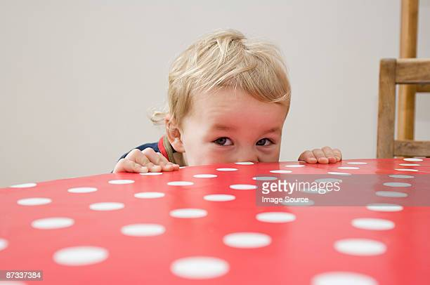 Boy looking over table