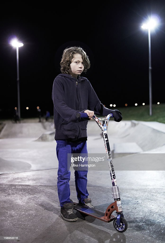 Boy looking straight to camera holding scooter : Stock Photo
