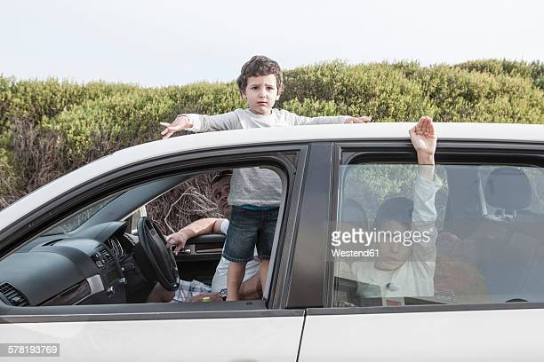 Boy looking through a sunroof of family car