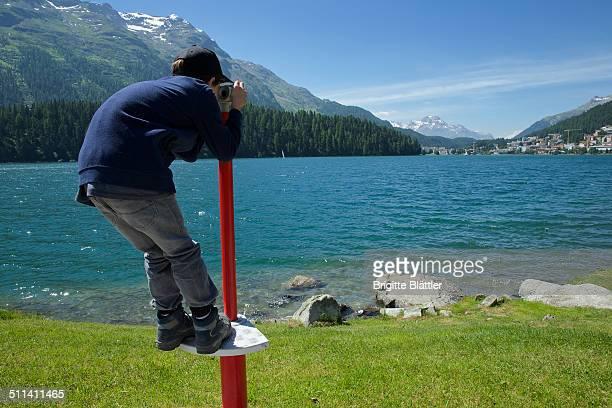 Boy looking through binocular at lake St. Moritz