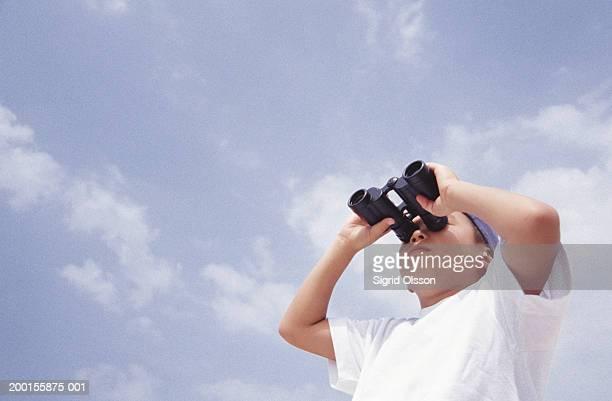 Boy (8-10) looking through binoculars, low angle view