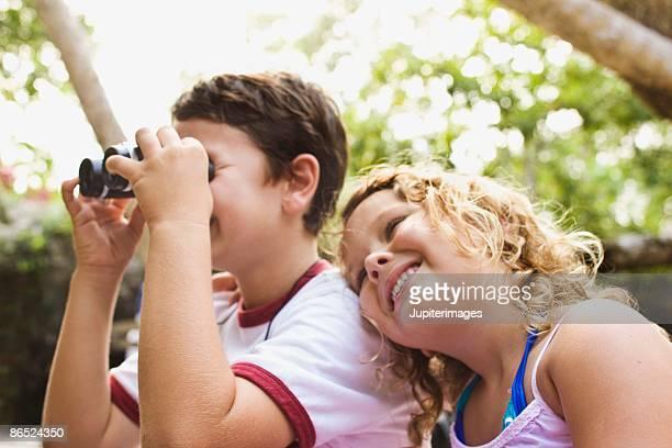 Boy looking through binoculars with girl