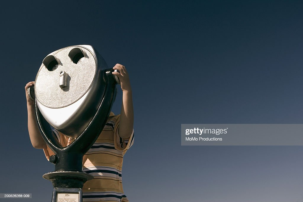 Boy (5-7) looking through coin operated viewer : Stock Photo