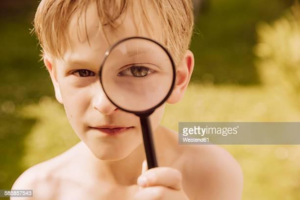 Boy looking through magnifier