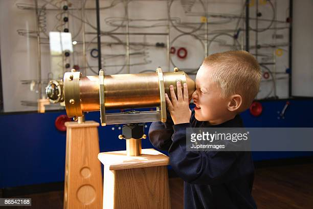 Boy looking through telescope at museum