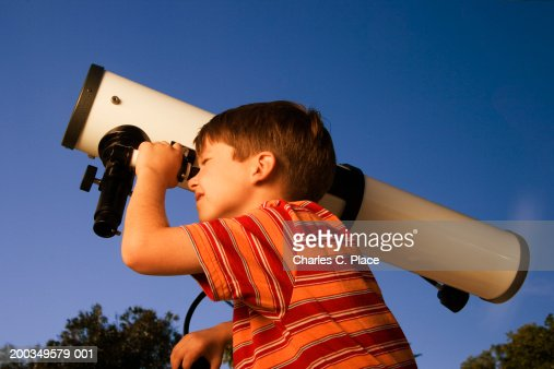 Boy (6-8) looking through telescope, close-up, side view, dusk : Stock Photo