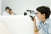 Boy looking through video camera, couple in background, side view