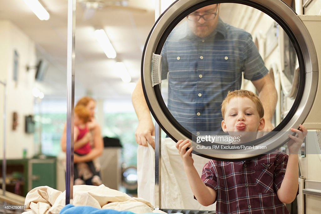 Boy looking through washing machine door and pulling funny face