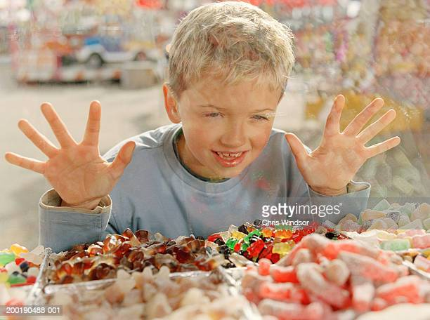 Boy (7-9) looking through window at sweets, pressing hands on glass