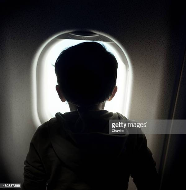 Boy looking through window on airplane