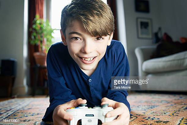 boy looking to camera playing with games console