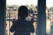 little boy looking to the window outdoor