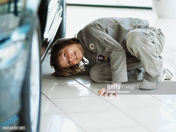 Boy (9-11) looking under car