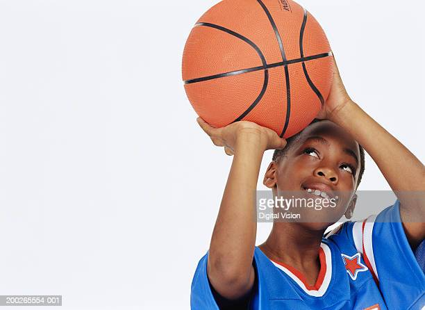 Boy (9-12) looking up aiming basketball, smiling