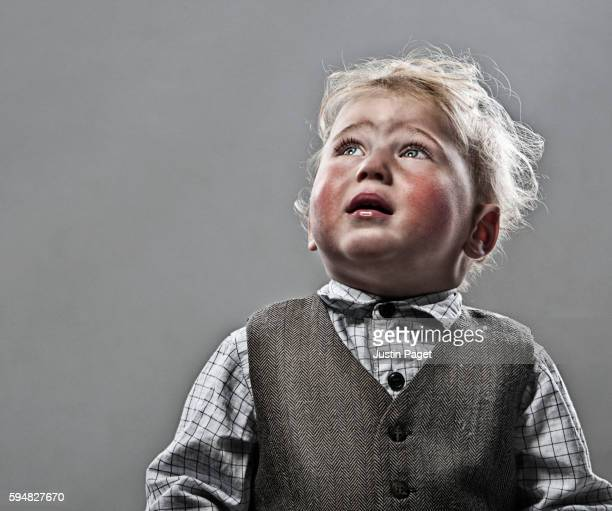 Boy (1-2) looking up and crying