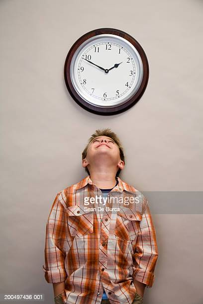 Boy (9-11) looking up at clock