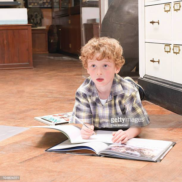 Boy looking up from book and note pad