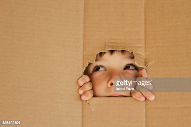 Boy looking up through a hole on cardboard
