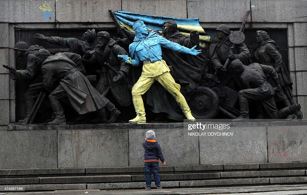 A boy looks at a figure painted in the colours of Ukraine on the monument of the Soviet Army in central Sofia on February 23, 2014. The main Soviet army monument in Sofia received a pro-Ukraine makeover early February 23 after massive pro-European protests in the former Soviet country turned deadly in the past week. AFP PHOTO / NIKOLAY DOYCHINOV