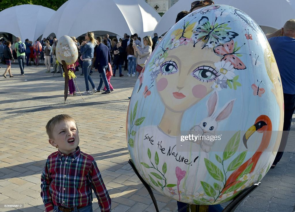 A boy looks at a huge 'Pysanka', a traditional Easter egg, during the celebrations of Orthodox Easter as part of the Pysanka festival in Kiev on May 1, 2016. 374 huge eggs and 40 000 small ones decorated by Ukrainian artists are displayed at St. Sophiya square in Kiev. / AFP / -