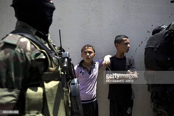 A boy looks at a masked Palestinian militant during the funeral of Mohammed alAwour in Beit Lahia northern Gaza Strip on June 12 2014 An Israeli air...