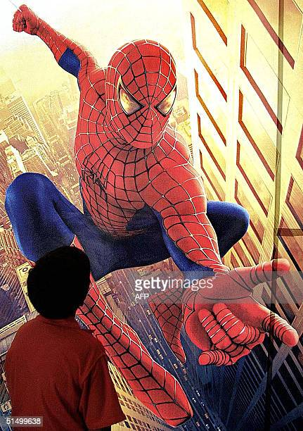 A boy looks at a poster of the movie 'Spiderman' at theatre in Bombay 24 May 2002 The movie already a box office success in the US was released today...