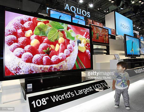 A boy looks at a prototype model of the world's largest 108inch sized LCD TV produced by Japan's electronics giant Sharp at Asia's largest...
