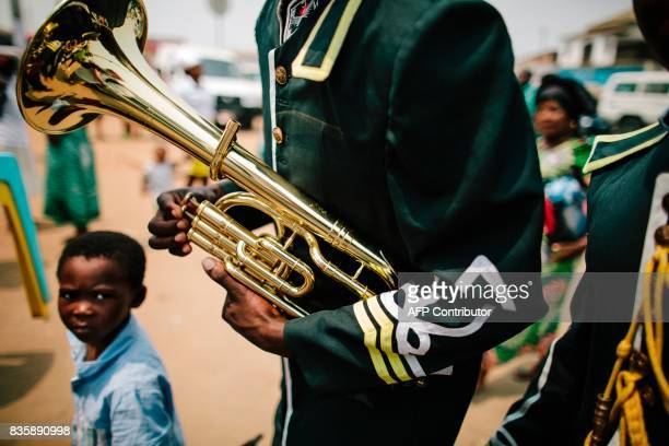 A boy looks at a trumpet held by a member of a marching band who enters the Kimbanguist Church founded by Simon Kimbangu a religious movement...