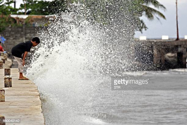 A boy looks at a wave as it hits the seawall along the boulevard in Surigao City on the southern Philippines island of Mindanao on December 6 2014...