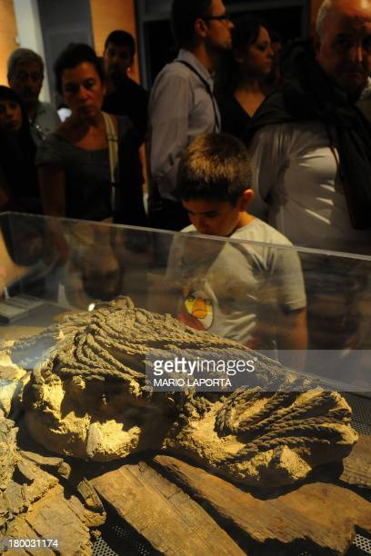A boy looks at boat ropes from ancient Herculaneum at an exhibition in the Hercolaneum Ruins Museum in Ercolano the city destroyed by the Mount...