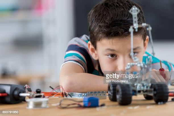 Junge schaut Roboter schuf er in Technologie-Klasse