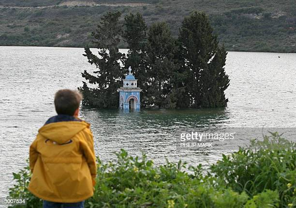 A boy looks at the belfry of the submerged church of Alassa village which lies in Cyprus' largest dam Kouris 23 February 2004 Kouris which holds...